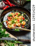 Fried shrimps on pan with fresh herbs - stock photo