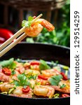 Closeup of fried shrimp on chopsticks - stock photo