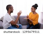 smiling young couple sitting on ... | Shutterstock . vector #1295679511