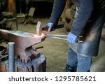 a blacksmith forges iron parts. ... | Shutterstock . vector #1295785621