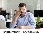 office worker sitting at desk... | Shutterstock . vector #1295889337