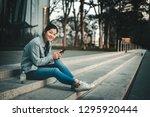 woman using smartphone on street | Shutterstock . vector #1295920444