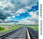 railroad to horizon under dramatic sky - stock photo