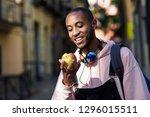 young black man eating an apple ... | Shutterstock . vector #1296015511