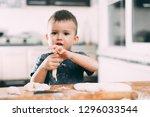 the child makes dough dumplings ... | Shutterstock . vector #1296033544