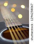 Small photo of Black acoustic guitar neck with oscillating strings