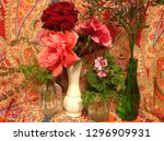 Small photo of A collection of roses, statice, geraniums, and African blue basil against a riotous paisley background