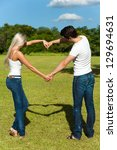 Portrait of young couple casting shadow of love symbol with arms. - stock photo