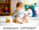 adorable baby girl playing with ... | Shutterstock . vector #1297104637