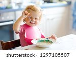 adorable baby girl eating from... | Shutterstock . vector #1297105507