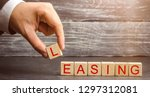 Small photo of Man puts cubes with the word Leasing. A lease is a contractual arrangement calling for the lessee to pay the lessor for use of an asset. Property, buildings, vehicles are common assets that are leased