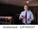 male winemaker giving tour... | Shutterstock . vector #1297459237