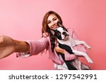 Stock photo amazing red haired girl making selfie with bulldog indoor photo of laughing positive female model 1297542991
