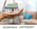 businessman holding house model ... | Shutterstock . vector #1297555357