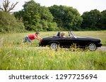 man pushing woman in broken... | Shutterstock . vector #1297725694