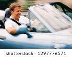 smiling man driving convertible ... | Shutterstock . vector #1297776571