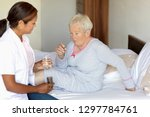 female care assistant giving a... | Shutterstock . vector #1297784761
