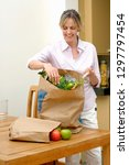 smiling mature woman unpacking... | Shutterstock . vector #1297797454