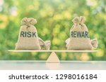 Small photo of Risk reward ratio / risk management concept : Risk and reward bags on a basic balance scale in equal position, depicts investors use a risk reward ratio to compare the expected return of an investment