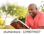 mature man reading outside.   Shutterstock . vector #1298074027