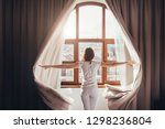Small photo of Rear view - young fit woman in home clothes opens curtains of bedroom window. Young girl is ready for new plans and new challenges. Concept of opening yourself to world, new affairs and new promises