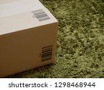 cardboard box on green carpet | Shutterstock . vector #1298468944