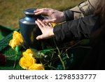 Hands Touching A Burial Urn In...