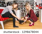 a seller propose to try shoes... | Shutterstock . vector #1298678044