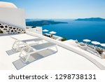 Small photo of Two chaise lounges on the terrace with sea view. Santorini island, Greece