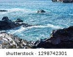 waves splashing against the... | Shutterstock . vector #1298742301