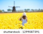 child in tulip flower field... | Shutterstock . vector #1299087391