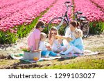 family picnic at tulip flowers... | Shutterstock . vector #1299103027