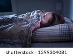 Stock photo scared woman hiding under blanket afraid of the dark unable to sleep after nightmare or bad dream 1299304081