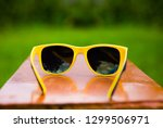 sunglasses on the bench on the... | Shutterstock . vector #1299506971