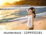 free woman enjoys ocean breeze... | Shutterstock . vector #1299552181
