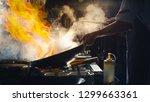 chef stir fry in wok. dramatic... | Shutterstock . vector #1299663361
