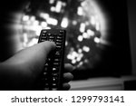 female hand holding tv remote... | Shutterstock . vector #1299793141