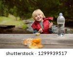 little boy is eating snacks... | Shutterstock . vector #1299939517