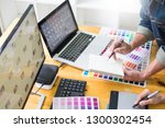 Stock photo graphic designer team working on web design using color swatches editing artwork using tablet and a 1300302454
