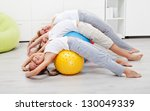 Happy healthy people exercising at home on large gymnastic balls - stock photo