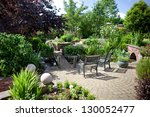 Beautiful landscaped garden with trees, pond, bridge over the pond - stock photo