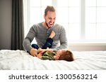 a father and son on bed playing ... | Shutterstock . vector #1300563214
