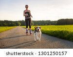 Stock photo girl skating with dog outdoors in nature on a road to forest sunny day countryside sunset 1301250157