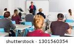 smiling male teacher giving... | Shutterstock . vector #1301560354