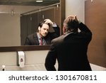 Small photo of Business man in office bathroom. Stressed manager using restrooms, washroom and lavatories while looking at receding hairline. Male beauty in public toilet with businessman checking hair loss