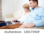 Happy young couple sitting on couch using laptop - stock photo