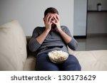 Scared man watching tv hiding his eyes - stock photo