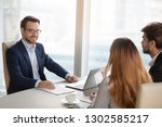 Small photo of Smiling adviser manager or negotiator consulting business people at meeting, successful businessman negotiating with partners, investor considering deal with clients, corporate executives cooperating