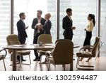 Small photo of Diverse multiethnic employees standing separately talking at work, caucasian business people avoid african and asian colleagues in modern office as racial segregation discrimination prejudice concept