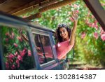 smiling girl in a camper van... | Shutterstock . vector #1302814387